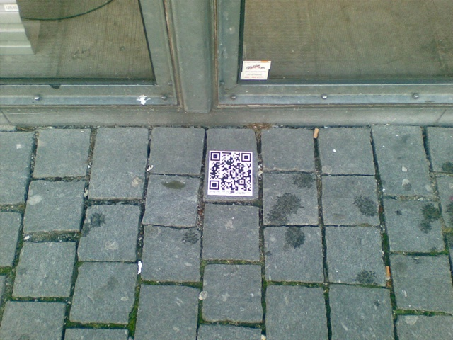 Picture of a QR code sticker by a shop window in Breda