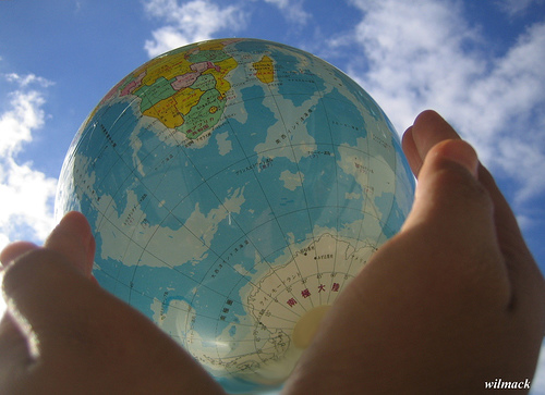 Two hands holding up a globe